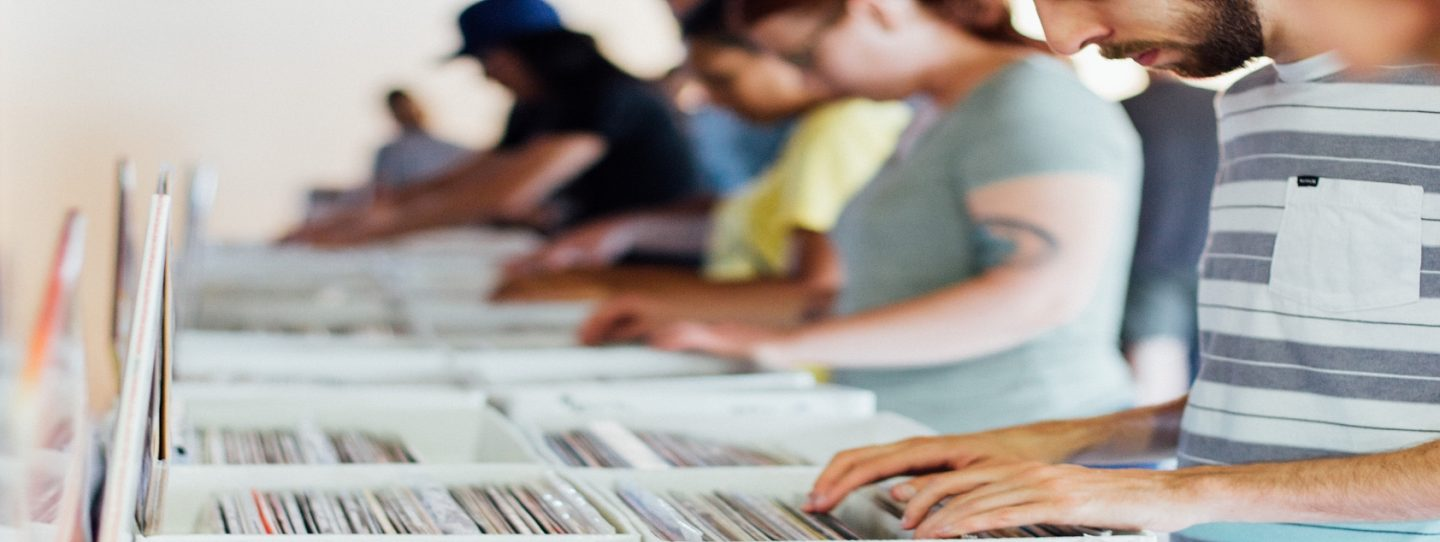 people searching through boxes of vinyl records in a line
